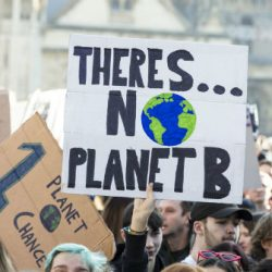 Demonstrators in the street with message There Is no Planet B on a placard.