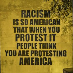 photo of a wall mural that states: Racism is so American that protest it and peple think you are prtesting America.